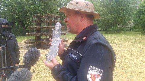 Sprengmeister Schwitzke hält einen Bombensplitter in der Hand.
