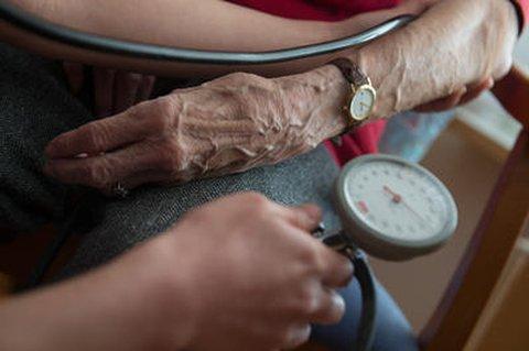 Eine Bewohnerin einer Seniorenwohnanlage bekommt den Blutdruck gemessen.