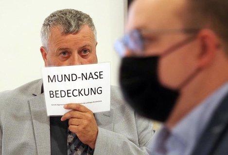 Michael Hanko hält sich während der Landtagssitzung ein Schild vors Gesicht.
